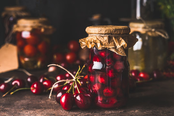 Cherry fruit compote in glass jars on dark rustic kitchen table. Close up. Preserved organic food from garden. Canning and conservation of harvest. Healthy homemade food Wall mural
