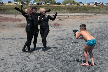 People, covered with mineral-rich mud, take pictures on a bank of Chokrak lake in Crimea