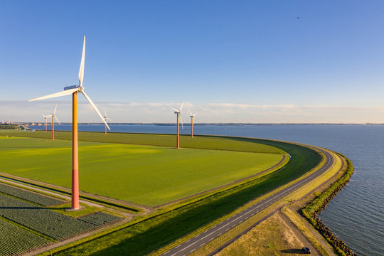 Wind turbines in a field in the Netherlands, next to a curved dike at a lake near Amsterdam.