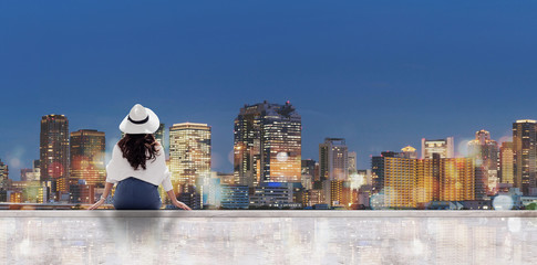Wall Mural - Traveling at night in the city. a woman in white hat sitting on patio looking at Osaka city at night