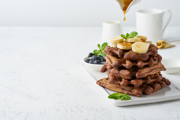 Chocolate banana waffles with maple syrup on white table, copy space, side view. Sweet brunch, maple syrup drop.