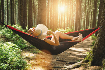 Woman relaxing at the forest on a hammock