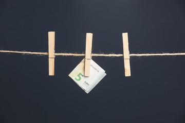Billetes de euro, colgados de una cuerda sujetos por pinzas de madera de extender la ropa