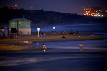 A power station is seen in the background as beachgoers are seen along the shore of the Mediterranean Sea in the evening at a beach in Ashkelon, Israel