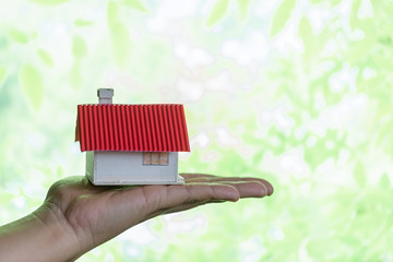 Human hands holding model of dream house, loans and investments concept