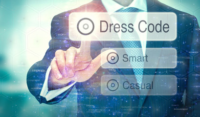 A businessman selecting a button on a futuristic display with a Dress Code concept written on it.