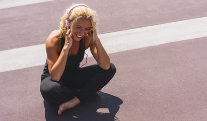 Young woman listening to music with earphones for fitness motivation. Portrait of a smiling young woman in sportswear relaxing sitting getting inspired. copyspace for your individual text.