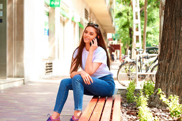 Young woman sitting on bench on the street and using her mobile phone