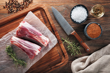 Raw lamb drumstick on white cooking paper and wooden cutting table. Dercorated with herbs, spices, chef's knife and napkin