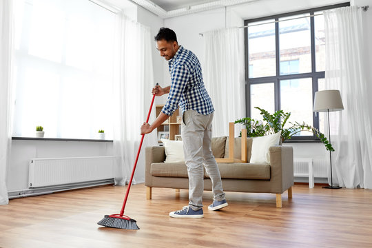 cleaning, housework and housekeeping concept - indian man with broom sweeping floor at home