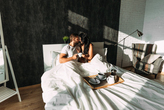 Man and woman in bed. Loving couple in bed. Breakfast in bed. Happy couple in bed. The relationship between a man and a woman. Loving couple. Family at home. Morning lovers. Family relationships.