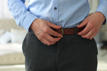 A man in grey pants and a blue shirt buttoned a brown leather trouser belt.
