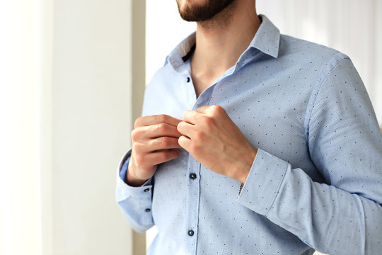 Man buttons sleeves on blue linen dress shirt in bedroom at slight angle.