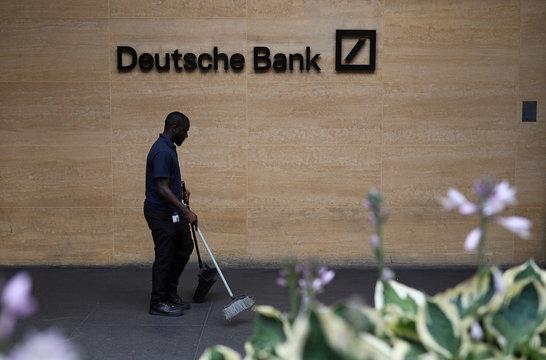 A worker cleans floor neat a Deutsche Bank office in London