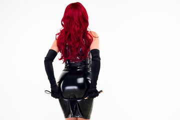 The red-haired passionate lady in a black latex dress is standing with her back holding the backside with a spank
