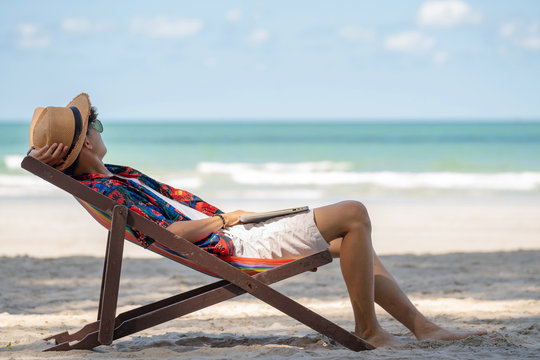 Young adult happy asian man tourist relax sunbathing sleep nap on beach chair or sun bed on tropical island sand beach in summer holiday vacation travel with blurred sea, beach and sky backgrounds