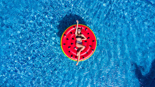 Top view of young woman relaxing on watermelon in pool. Young girl floating with fruit mattress. Summer holiday, luxury lifestyle and fashion concept