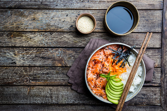 Hawaiian salmon poke bowl with seaweed, avocado, carrot, sesame seeds and rice. Top view, overhead, flat lay
