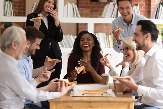 Cheerful multiracial office business people laugh share takeaway pizza together
