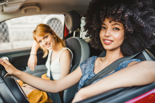 Two young women friends driving in the city - Millennials use the car to get around - People look towards the camera