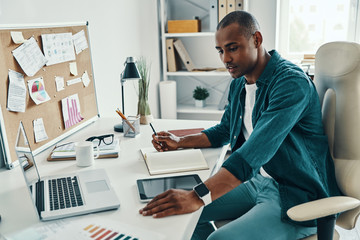 Confident businessman. Thoughtful young African man in shirt using laptop while sitting in the office