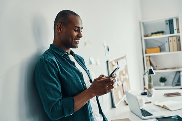 Texting someone. Handsome young African man in shirt using smart phone while standing in the office
