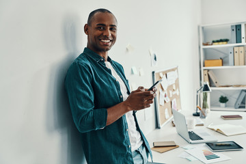 Confident businessman. Handsome young African man in shirt using smart phone and smiling while standing in the office