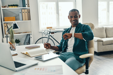Time for lunch. Handsome young African man in shirt checking the time and smiling while working in the office