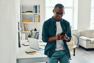 Using new mobile app. Handsome young African man in shirt using smart phone while standing in the office
