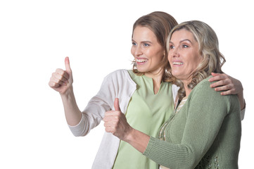 Portrait senior woman with daughter with thumbs up on white background