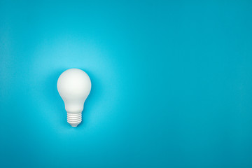white light bulb is shine on blue table. - business growth and great ideas concept. Fototapete