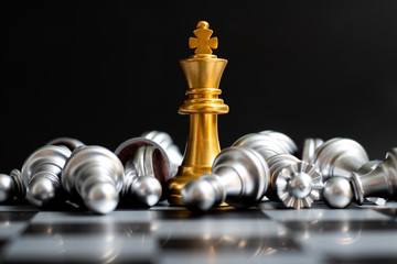 Gold king chess piece win over lying down silver pawn on black background