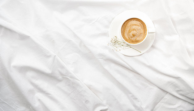 Morning flatlay in white bed. Coffee and morning routine. Copy space. Concept minimalism