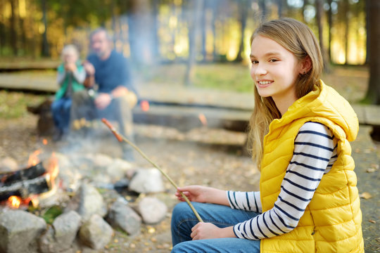 Cute little sisters and their father roasting marshmallows on sticks at bonfire. Children having fun at camp fire. Camping with kids in fall forest.