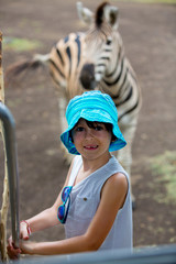 Child enjoying herd of zebras and ostrich in the wild in park