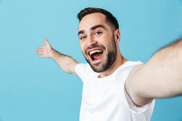 Excited young happy bearded man posing isolated over blue wall background take a selfie by camera.