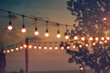 blurred bokeh light on sunset with yellow string lights decor in beach restaurant Wall mural