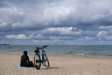 Foto op Plexiglas Fiets Poland, Gdansk, Baltic Sea - women in black cloth sitting on the beach with bike in cloudy day with amazing dramatic clouds