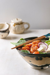 Poke bowl with soy sauce marinated salmon, rice, avocado and tofu cheese served in ceramic bowl with chopsticks and teapot on white marble table. Copy space