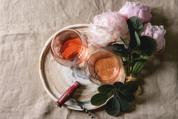 Two glasses of different rose wine standing on grey linen table cloth with pink peonies flowers and vintage corkscrew. Romantic greeting card. Flat lay, space