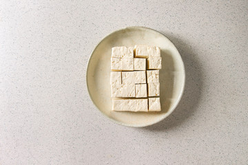 Cutting cubes of tofu, traditional japanese soy cheese in ceramic plate over grey spotted background. Flat lay, space