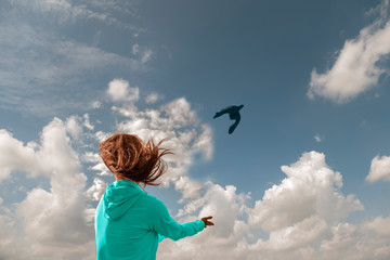 conceptual image of freedom, a girl with her hair flying in the wind lets a bird go into the blue sky.