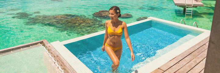 Wall Mural - Luxury travel vacation at Bora bora overwater bungalow hotel honeymoon suite room with infinity swimming pool bikini woman enjoying blue ocean view. Tropical summer lifestyle.