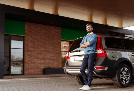 Confident man leaning on car