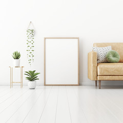 Poster mockup with vertical frame  standing on floor in living room interior with tan brown leather sofa, green pillow and plants in pots on empty white wall background. 3D rendering, illustration.