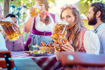 Frau in Tracht schaut in die Kamera während sie ein Bier in Bayern trinkt