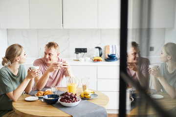 Young restful spouses sitting by served table in the kitchen, having brunch and tea and talking