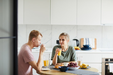 Young woman and her husband drinking orange juice by breakfast in the morning