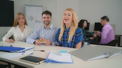 Coworkers wish a happy birthday with cake and candle. Employees enjoy party singing song in meeting room. Young people in startup company wearing casual clothes with happy smile sitting at the desk.