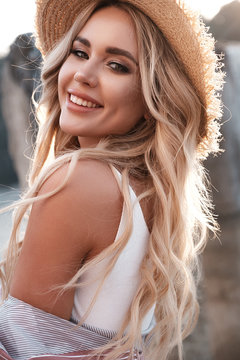 Closeup portrait of a romantic young woman in a straw hat. Laughing girl enjoying her time outside in park with sunset in background. Natural lifestyle, summer outdoor photoshoot, summertime